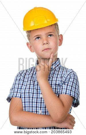 Half-length emotional portrait of a thoughtful boy wearing blue t-shirt and yellow hardhat, isolated on white background.