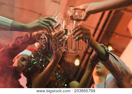 partial view of friends clinking glasses of champagne while having new year party