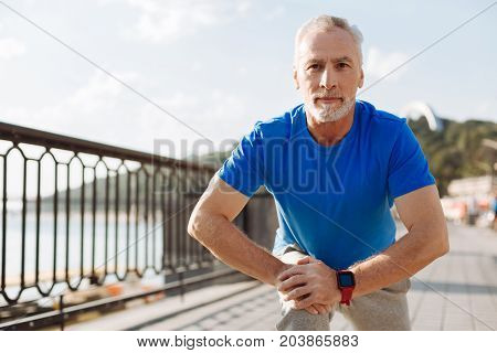 Keeping fit. Athletic handsome senior man doing lunges while stretching himself during a morning run