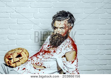 Halloween Man Sitting With Pumpkin On White Brick Wall