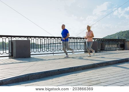 Energetic run. Energetic athletic senior man and woman jogging together in the morning while trying to keep fit