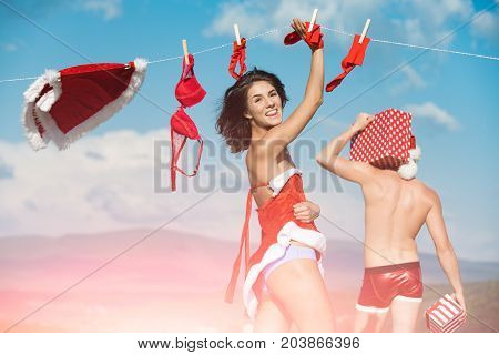Xmas red costume on rope with pin. New year guy with muscular body on blue sky. Couple in love of man and girl hanging clothes for drying. Laundry and dry cleaning. Christmas man and woman family.