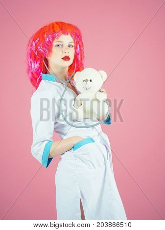 Nurse on pink background. Doctor and patient. Health care and cure concept. Girl examining teddy bear toy with stethoscope. Woman wearing medical uniform and red wig.