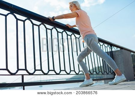 Increasing suppleness. Fit senior woman resting her hands on the balustrade and performing stretching while warming up before morning run