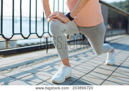 Preparation for jogging. The close up of a slender elderly woman doing lunges on the bridge while warming up before jogging