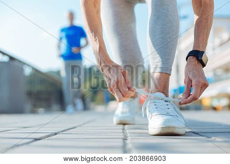 Ready to jog. The close up of hands of an athletic elderly woman tying shoelaces on the sneakers while running in the morning together with her husband