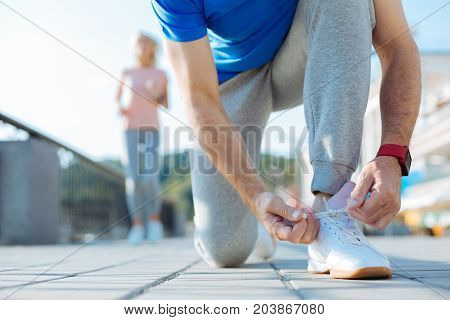 Ready to jog. The close up of an athletic senior man kneeling on the ground and tying shoelaces on his sneaker while an woman in a pink t-shirt jogging in the background