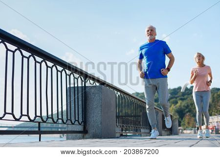 Forever young. Pleasant energetic elderly man and woman running down the bridge while exercising in the morning