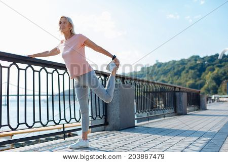 Supple muscles. Charming senior woman holding on to the bridge balustrade and performing leg stretching before her morning run