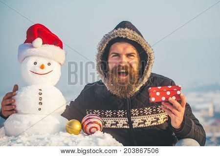 Happy Hipster And Snowman In Santa Hat On Grey Sky