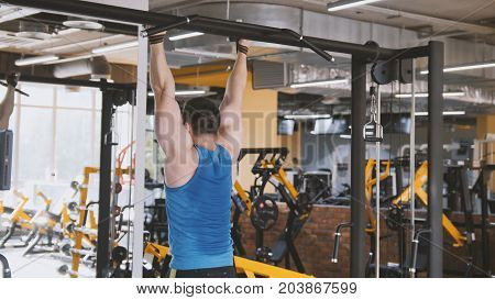 Male athlete - bodybuilder doing pull-up bar abdominal exercise in gym, close up
