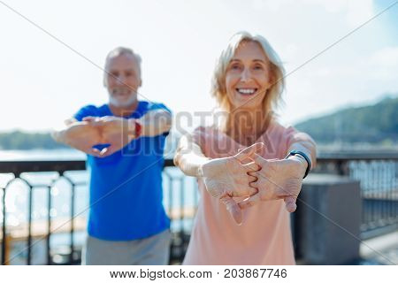 Energetic workout. Pleasant cheerful senior man and woman holding hands in a lock and performing stretching exercises while working out