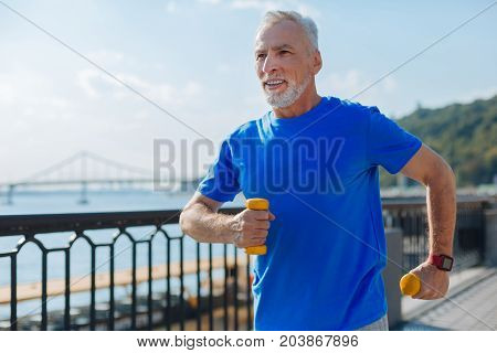 Thorough workout. Pleasant handsome senior man holding yellow dumbbells in both hands and jogging with them