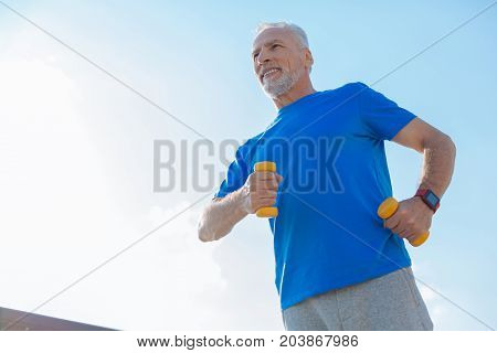 Energetic man. Pleasant athletic senior man running down the street while holding dumbbells in both hands