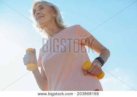 I love running. Pleasant cheerful senior woman running in the streets and holding dumbbells while smiling