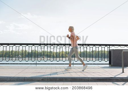 Brisk workout. The side view of an athletic senior lady jogging down the bridge while training thoroughly and keeping fit