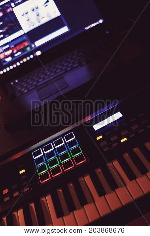 Details of a modern midi keyboard and laptop in blurry background.