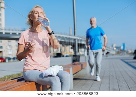 Need some rest. Pleasant senior woman sitting on the bench and drinking water, resting after a morning run while a man jogging in the background