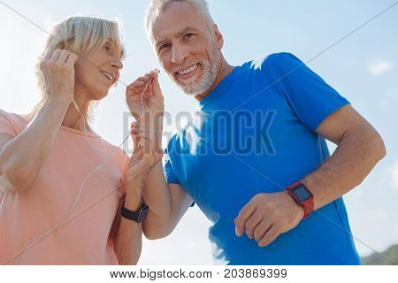 Sharing best things. Lovable elderly couple having a break in the morning run and listening to the music, sharing one pair of headphones
