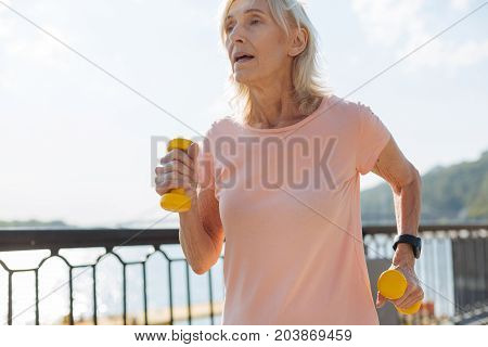 Extra exercise. Pleasant senior woman running in the waterfront area while holding a pair of yellow dumbbells
