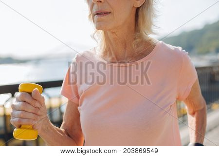 Senior sports lover. The close up of a chest area of an energetic senior woman working out with a yellow dumbbell in her hand