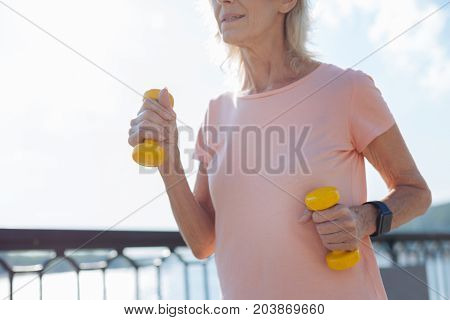 In nice shape. The focus being on the hands of an athletic elderly lady standing on the bridge and working out with two yellow dumbbells