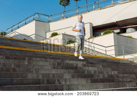 Love exercising. Handsome well-built senior man running down the stairs while having his morning run