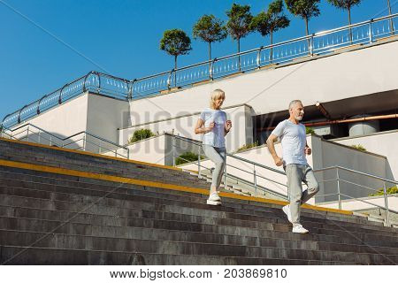 We love sports. Energetic athletic senior couple running down the stairs while having their morning run together
