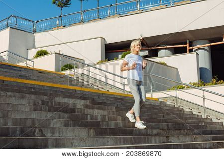 Enjoy jogging. Slender athletic senior woman running down the stairs while jogging in the waterfront area