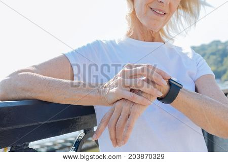 Love punctuality. The close up of delicate hands of a smiling elderly woman looking at her smart watch, trying to keep up with her daily schedule