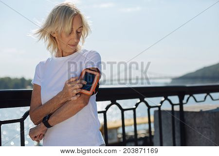 Convenient accessory. Athletic elderly woman pressing the touchscreen of her phone being in the protective arm band suitable for running