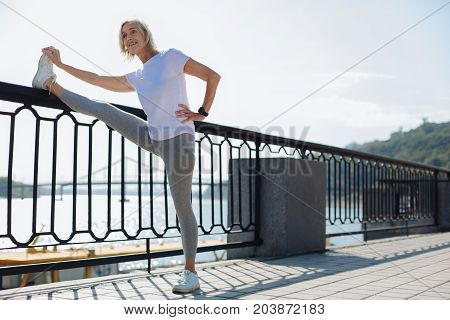 Excellent suppleness. Upbeat athletic senior woman holding her leg on the top of a bridge balustrade while performing stretching exercises and demonstrating good suppleness
