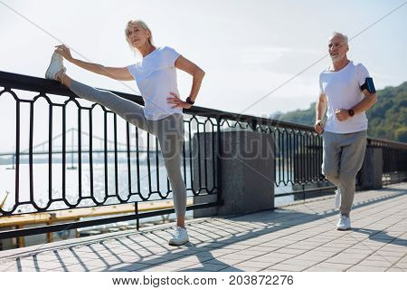 Mixed training. Pleasant athletic elderly lady putting her leg on the top of a bridge balustrade and stretching while her husband jogging