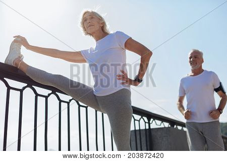 Dedicated athletes. Charming young woman doing stretching exercises and holding her leg on the top of a bridge balustrade while her husband running down the bridge