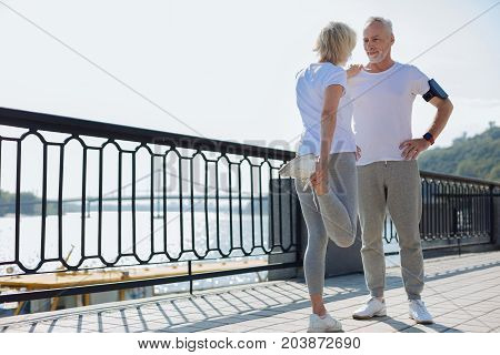 Let me help. Pleasant senior man standing still, holding hands on his waist and providing balance to his wife doing stretching exercises