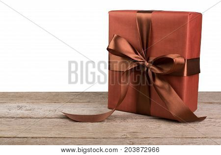 Gift box wrapped with maroon paper and brown satin ribbon on wooden table at white background. Modern presents for any holiday, christmas, valentine or birthday