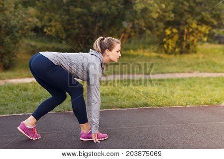 Pretty Sporty Woman In The Ready Set Go Position To Start Running In The Park