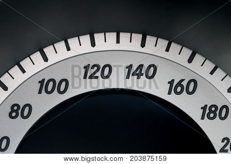 Closeup of the speedometer in silver and black from the interior of a vehicle