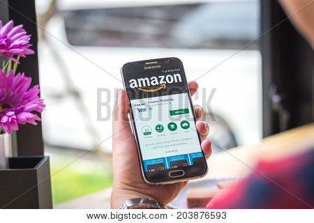 Chiang Mai, Thailand - September 12, 2017: Samsung Galaxy S6 smartphone launches amazon shopping application on the desk screen at the coffee shop.
