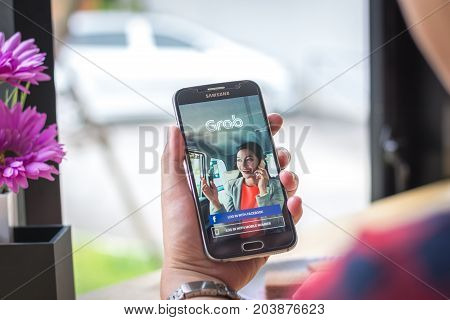 Chiang Mai, Thailand - September 12, 2017: Samsung Galaxy S6 smartphone launches grab driver application on the desk screen at the coffee shop.