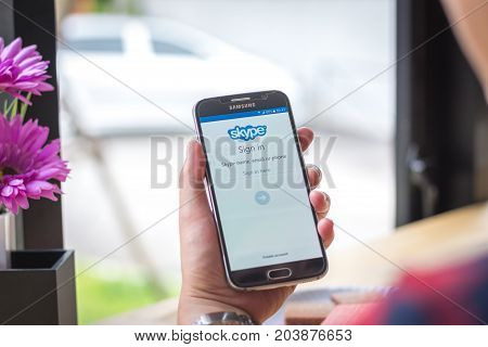 Chiang Mai, Thailand - September 12, 2017: Samsung Galaxy S6 smartphone launches skype application on the desk screen at the coffee shop.