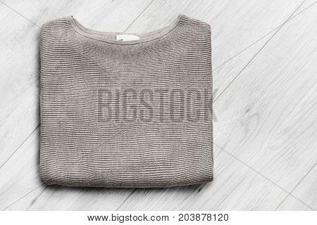 Folded beige basic pullover on white wooden background