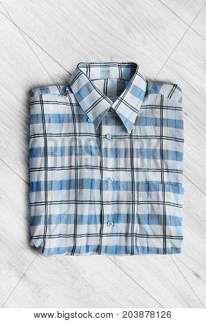 Blue tartan shirt folded on white wooden background