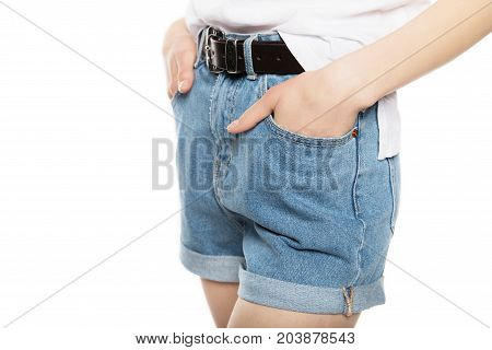close-up partial view of girl in denim shorts standing with hands in pockets isolated on white
