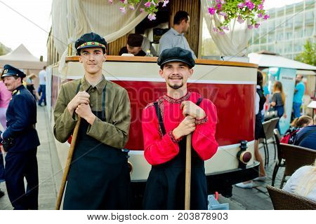 Vinnytsia Ukraine - September 09 2017: Birthday of the city of Vinnytsia. Two young men in a janitor's suit are standing by the tramcar.