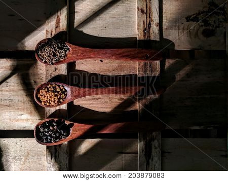 fenugreek, pepper and cumin seeds placed on wooden spoon