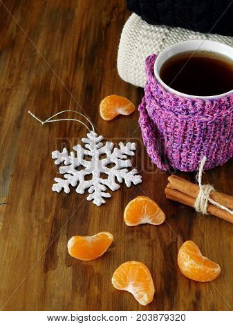 Tea in a mug wrapped into tiny scarf surrounded by mandarin segments