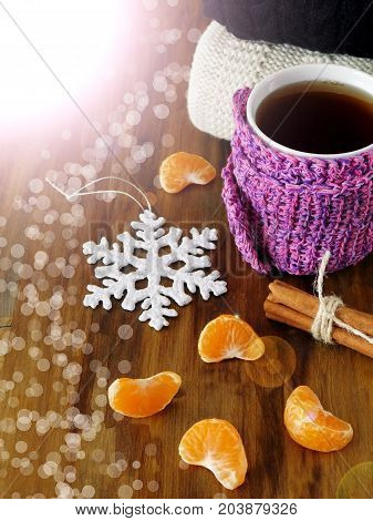Tea in a mug wrapped into tiny scarf surrounded by mandarin segments. Photo with special editing