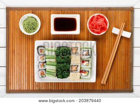 Japanese food restaurant delivery - sushi maki, unagi and roll platter set on mat on white wood background, above view
