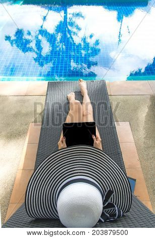 Asian Women lifestyle play laptop and relaxing near luxury swimming pool sunbath summer day at the beach resort in the hotel. Summer Concept.
